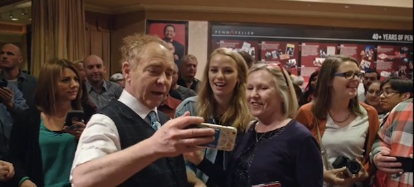 Teller taking a picture with magic fans
